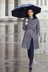Frau mit Regenschirm bei Herbstwetter