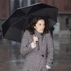 Frau zittert vor Kälte bei Regentag