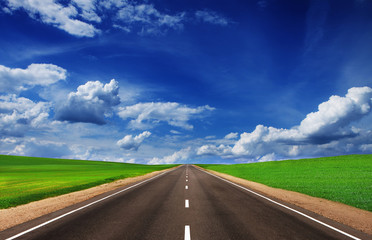 Asphalt road in green fields under beautiful sky