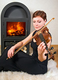 woman on sheepskin plays the viola.