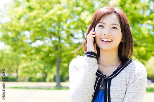 young asian woman using cellphone in the park