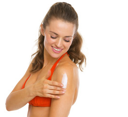 Happy young woman in swimsuit applying sun block creme