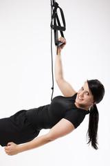 Sportlerin trainiert Bizeps mit Suspension Trainingsgerät