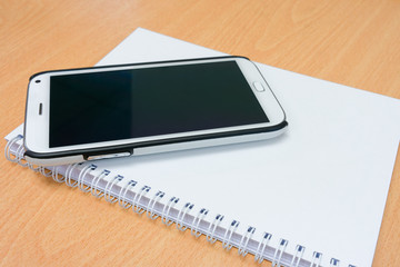 Conceptual image of smart phone and notebook on wooden table