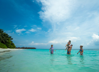 Family swims against the beautiful tropical island