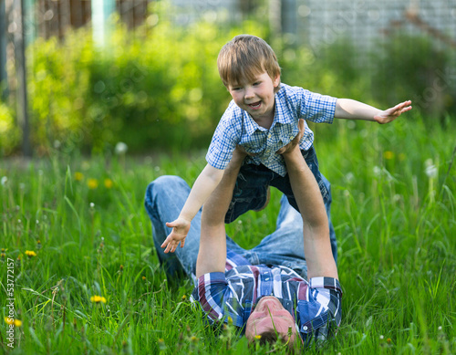 Father with his small son playing in the grass