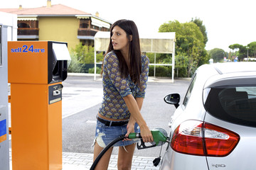 Young woman putting fuel to her car