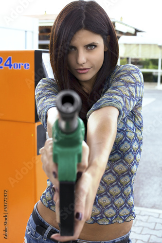 Portrait of female model holding and pointing gas gun