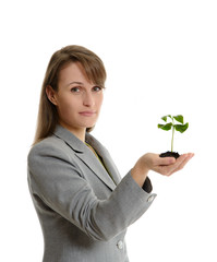 Beautiful business woman holding a handful of earth
