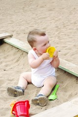 baby plays with sand mold on playground