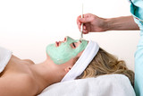Beautician applying green facial mask on a woman.