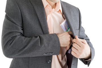 man puts a stack of banknotes in a pocket