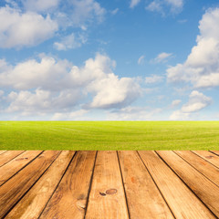 Wooden deck table over beautiful meadow with blue sky