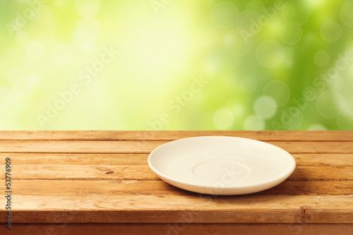 Empty plate on wooden table over bokeh background
