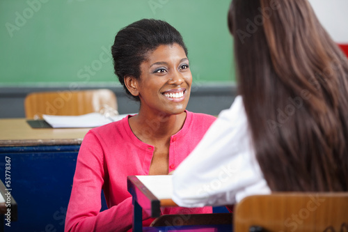 Teacher Looking At Teenage Schoolgirl At Desk