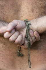 man's hands tied with chains
