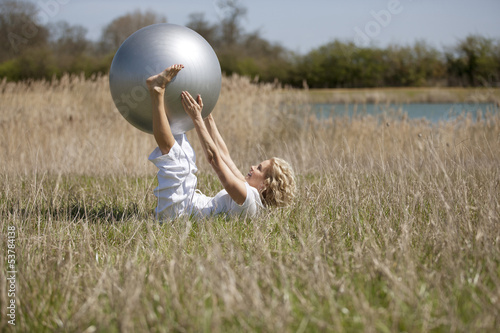 A mature woman exercising with an exercise ball