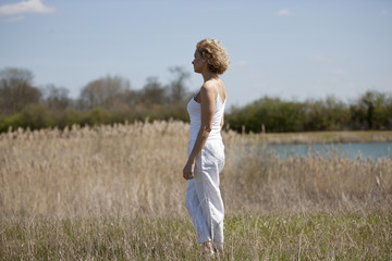 A mature woman standing in the countryside in summertime