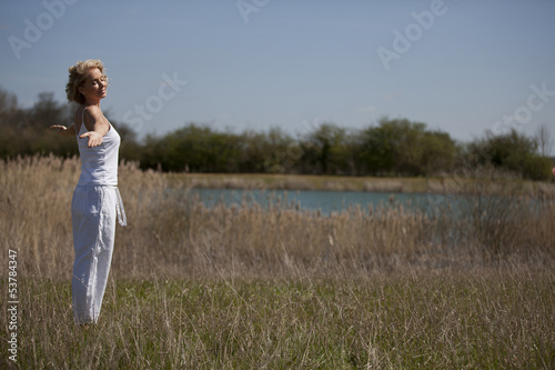 A mature woman practising yoga in the countryside in summertime