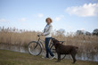 A mid adult woman pushing a bicycle next to a lake with her dog