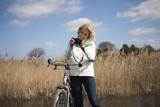 A mid adult woman looking at a camera whilst out cycling
