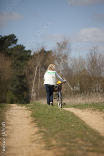 A mid adult woman pushing a bicycle along a country path