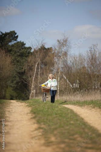 A mature woman pushing a bicycle along a country path
