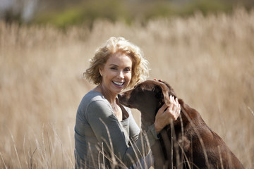 A mature woman sitting on the grass stroking her dog, smiling
