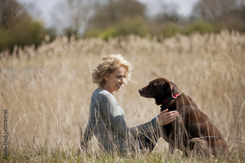 A mid adult woman sitting on the grass stroking her dog