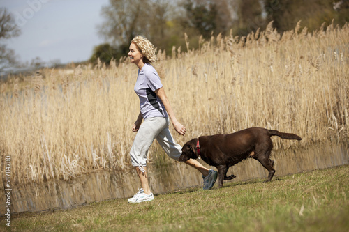 A mature woman walking in the countryside with her dog