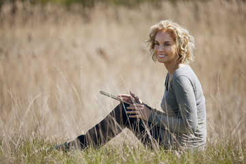 A mid adult woman sitting in long grass, using a digital tablet