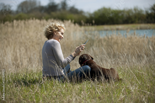 A mature woman looking at a digital tablet with her dog