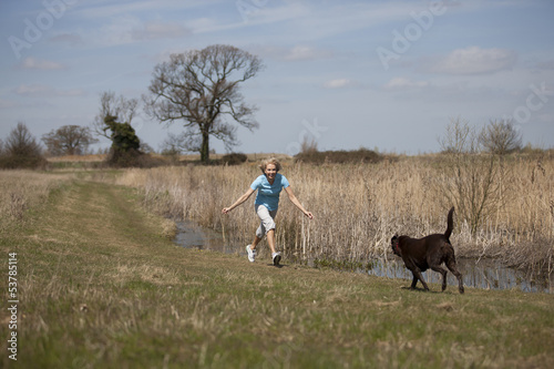 A mature woman having fun with her dog in the countryside