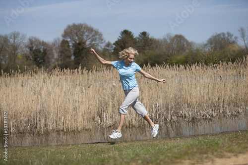 A mature woman jumping with arms outstretched in the countryside