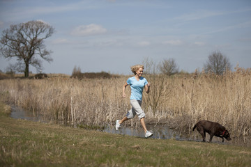 A mid adult woman running in the countryside with her dog