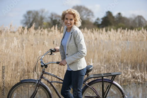 A mid adult woman standing beside a lake with a bicycle