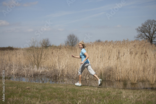 A mid adult woman running in the countryside