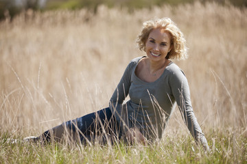 A mid adult woman sitting in the countryside, smiling to camera