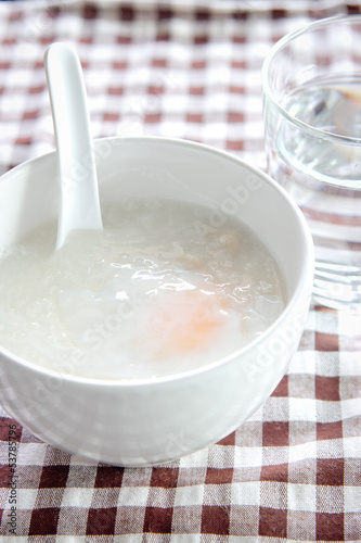 Rice porridge with egg in white bowl and a glass of water