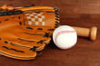 Baseball glove, bat and ball on wooden background