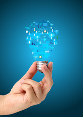 Light bulb in hand with technology business network