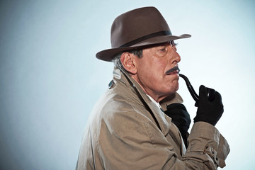 Vintage detective with mustache and hat. Smoking pipe. Studio sh