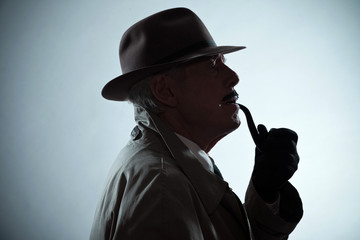 Silhouette of vintage detective with mustache and hat. Smoking p
