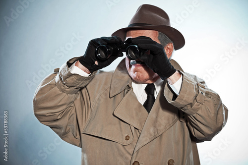 Vintage detective with mustache and hat. Looking through binocul
