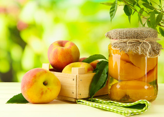 Jar of canned peaches and fresh peaches on wooden table,