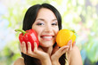 Girl with fresh peppers on natural background