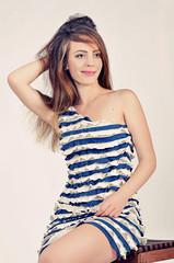молодая и очень красивая девушка в полосатом платьи