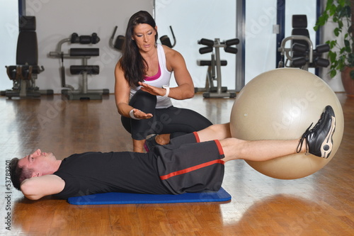 Man working out while female personal instructor assisting him