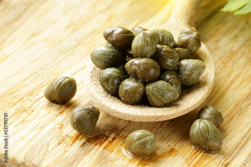 Pickled capers in a wooden spoon