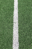 Photo of a green synthetic grass sports field with white line sh